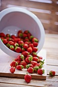 Fresh strawberries falling out of a colander