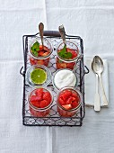 Fresh strawberries, cream and strawberry compote with mint in a wire basket
