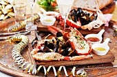 A wooden platter of grilled seafood with sauces, bread and salad