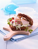 Wholemeal bread roll with radish creme and turkey ham