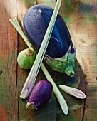 Assorted aubergines and lemongrass on a wooden surface