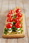 Toadstools made from cherry tomatoes and mozzarella, with sliced chives and spots of mayonnaise