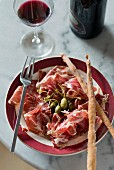 Parma ham with capers, grissini and red wine