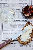 A slice of buttered bread, a sea urchin and a glass of white wine on a menu