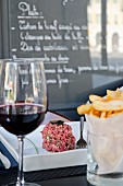 Beef tartar, crisps and a glass of red wine in a bistro