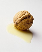 A walnut in a small pool of walnut oil