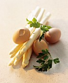 A still life of ingredients featuring white asparagus and eggs
