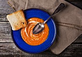 Top view on blue plate of pumpkin puree over old wooden table