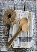 Rustic kitchen utensils: linen dish towel, twine and wooden spoon