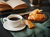 A cup of coffee and a croissant