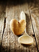 A heart-shaped potato and a wooden spoon on a wooden surface