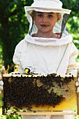 A girl holding a honeycomb covered with bees