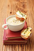 Creamy onion soup served with baguette topped with Camembert