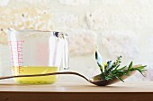 A still life featuring clear vegetable stock and fresh herbs