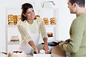 Woman at bakery helping customer