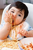 2 year old boy eating spaghetti