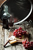 Bunch of red grapes with cheese and vintage bottle of red wine on old wooden table