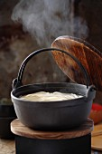 Steaming pot of soup with udon noodles