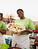 African American volunteer holding bowl of salad