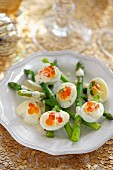 Quail's eggs with salmon caviar on green asparagus