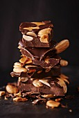 Several chunks of chocolate with nuts and almonds, stacked