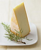 A wedge of Raclette cheese with a sprig of fresh rosemary on a plate