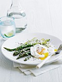 A poached egg with green asparagus and parmesan