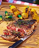 Grilled beef steak with corn on the cob on a garden table