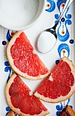 Pink grapefruit slices with sugar