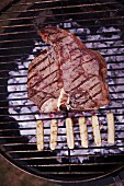 A T-bone steak and sausages on a barbecue