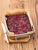 Chocolate cake with cranberries in a baking tin
