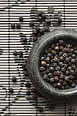 Black peppercorns in a mortar