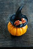 An ornamental pumpkin with a witches hat