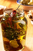 Olive oil with herbs, garlic and dried tomatoes in a screw-top jar