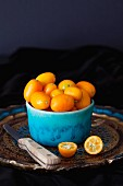 Kumquats in blue ceramic bowl