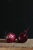 Two red onions against a dark background