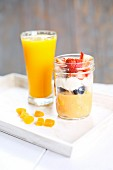 Papaya puree with berries served with coconut cream and orange juice