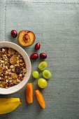 A bowl of muesli next to fresh fruit