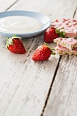 An arrangement featuring a bowl of yogurt, strawberries and strawberry rice crackers