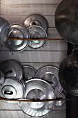 Arrangement of shiny pot lids and rusty pots