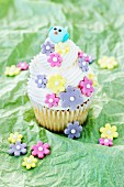A lemon cupcake decorated with sugar flowers and a bird