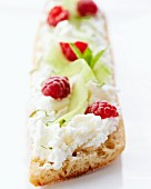 Slice of bread topped with cream cheese, cucumber and raspberries