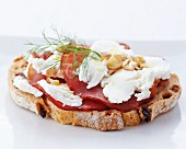 A slice of bread topped with cream cheese, ham and hazelnuts