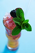 A cocktail with berries and a sprig of mint