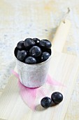 A mug of fresh blueberries on a chopping board
