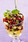 A fruit salad garnish with fresh mint