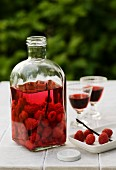 Home-made raspberry liqueur on a garden table