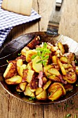 Fried potatoes with bacon in a pan