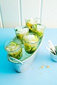 Five glasses of woodruff caipirinha in an ice bucket
