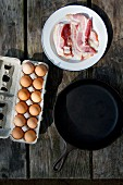 Raw bacon and eggs next to a cast-iron pan on a wooden table